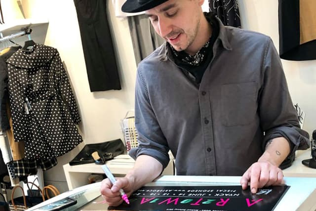 Artist Michael Delaney signs the limited-edition ART WALK poster, gearing up for the June 14-16 event. Courtesy Nyack ART WALK/Facebook.