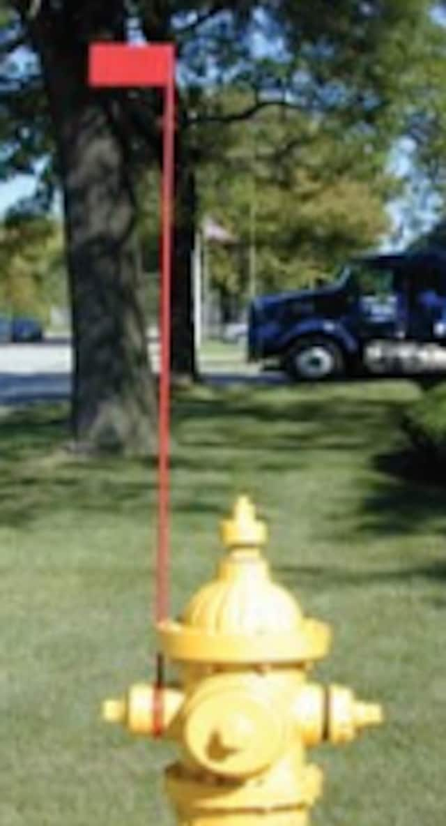 The red markers that will soon be affixed to fire hydrants in Scarsdale stand approximately three feet tall