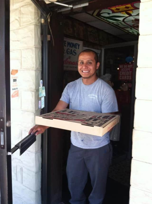A customer exits the fourth generation, family-run Barcelona's Restaurant & Bar in Garfield with a pizza.