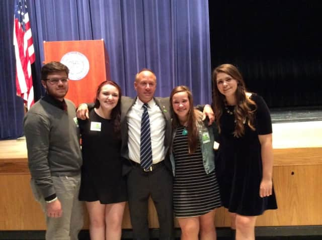 Mark Barden, father of a victim of the Sandy Hook shooting, embraces student leaders at Danbury High School who introduced the Say Something program at their school this fall.