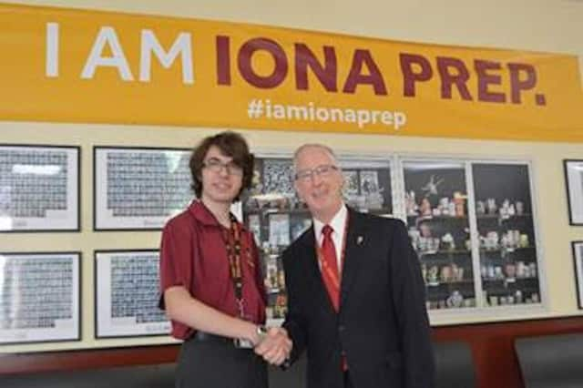 Brother Thomas R. Leto, president of Iona Prep in New Rochelle, congratulates Iain Pile of Tuckahoe,
