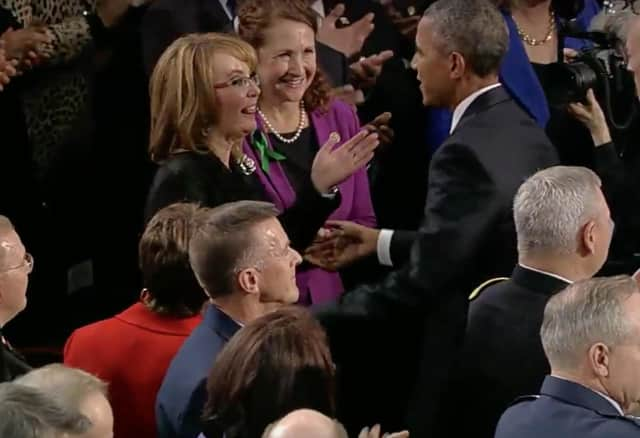 Gabrielle Giffords reaches out to President Barack Obama before the State of the Union Address. Giffords, a former Congresswoman and gun violence victim, was sitting with U.S. Rep. Elizabeth Esty.