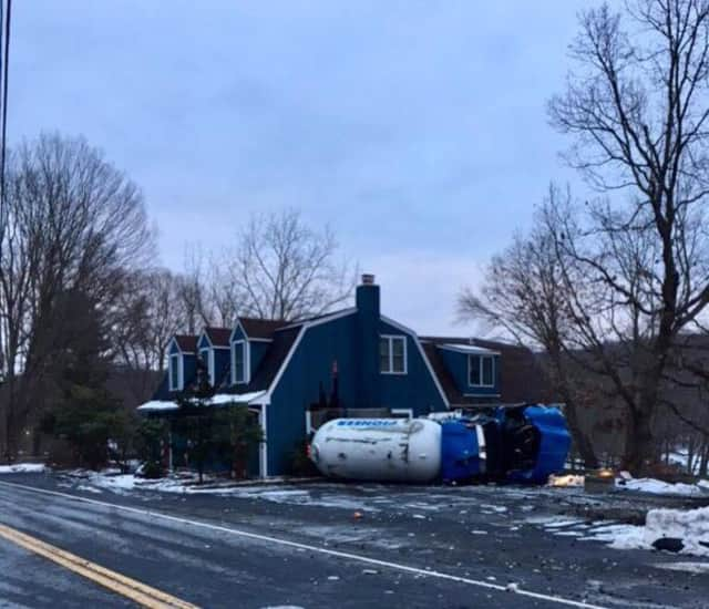 A Monroe truck driver was cited after the tanker truck full of propane he was driving went off the road and hit a house in Bethany