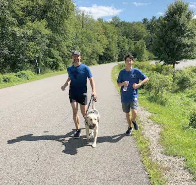 Thomas Panek runs with his son and his guide dog Blaze.