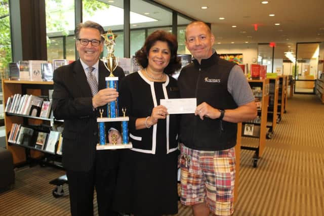 Wilton Library's executive director Elaine Tai-Lauria receives a generous donation of $1,200 from Mitch Ancona. Holding the trophy is Bocce Brawler Michael Crystal (husband of Janet Crystal, marketing communications manager for the library).