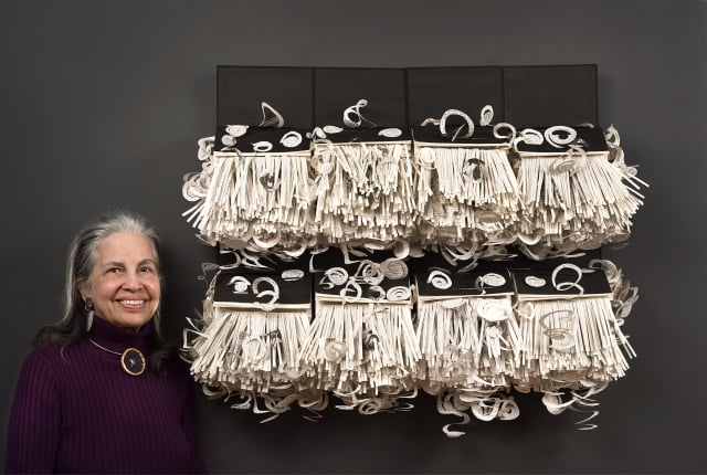 Irmari Nacht of Englewood and her large recycled bookwork — composed of 8 identical books cut into swirls, spirals, and strips.