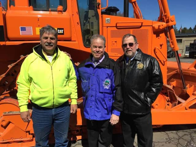 Rockland County Executive Ed Day and County Highway Superintendent Skip Vezzetti stand in front of a refurbished 1988 bulldozer.