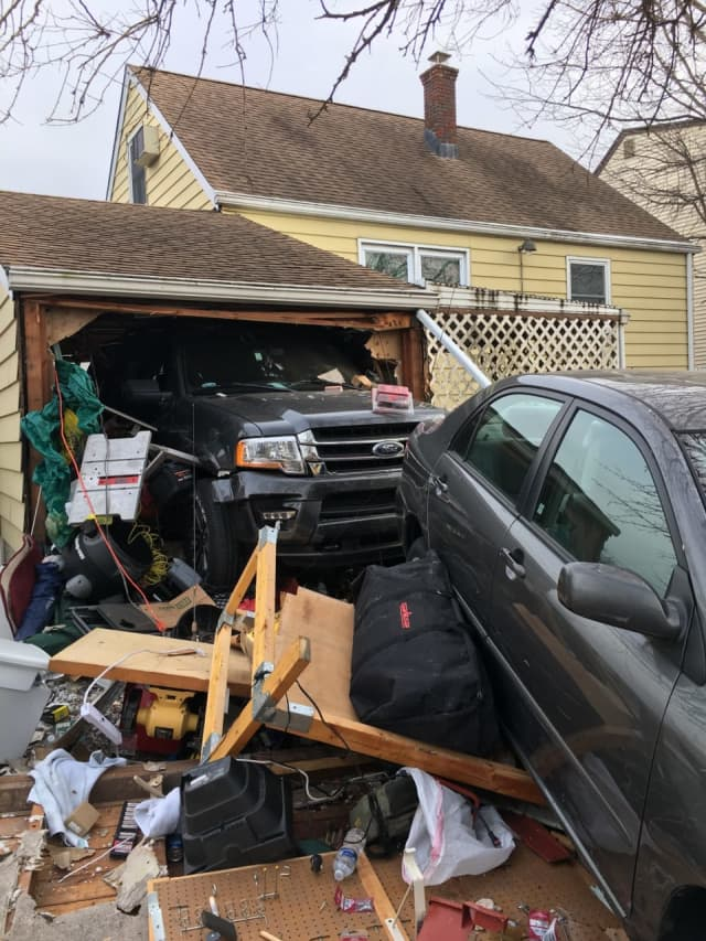 The Ford rammed the sedan straight through the back of the garage.