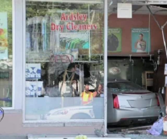 Clothes and debris lie scattered at the Ardsley Dry Cleaners Sunday after a woman drove her Cadillac through its front window. The store was closed at the time, but the bagel shop next door was packed with people having breakfast.