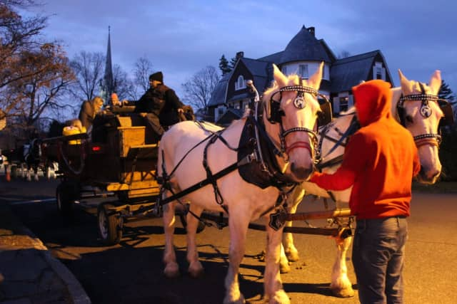 Families can climb onto the horse-drawn carriage rides in front of Pequot Library for a tour of picturesque Southport Village during the 2016 Holiday Caroling Party and Open House.