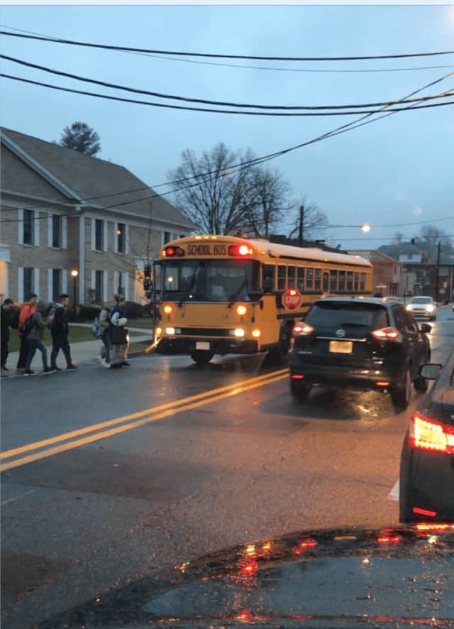 A car speeds past the school bus, ignoring the stop sign and blinking red lights in Wood-Ridge.
