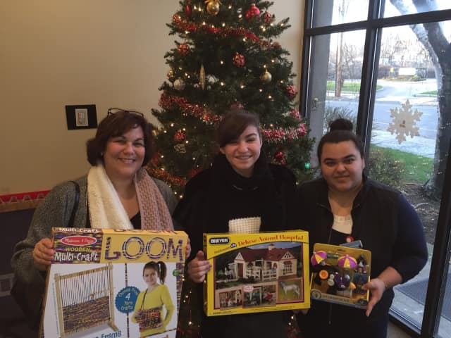 Trumbull resident Cindy Anelante, her daughter, Cassandra Anelante and Rosario Terron, lead bilingual advocate at The Center for Family Justice, with toys Cassandra collected.