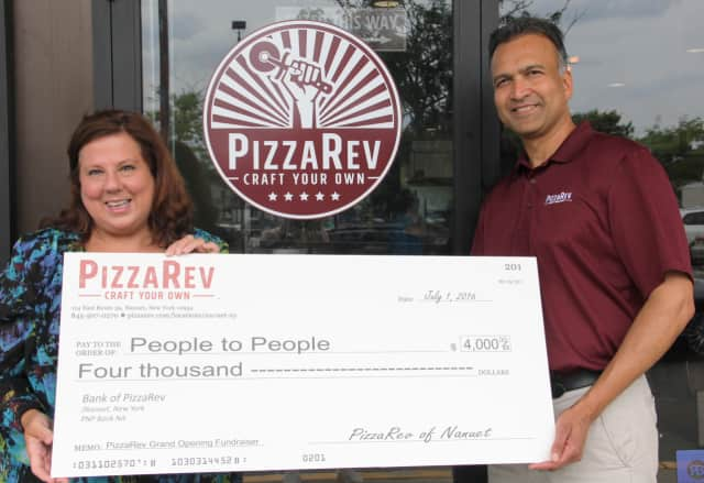 People to People Executive Director Diane Serratore is presented with a check for $4,000 by PizzaRev owner Satyen Shah.