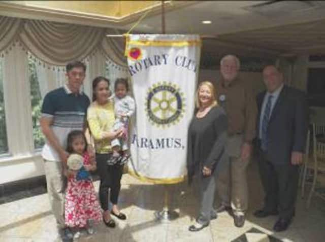Parents Albert and Joy Dela Pena with Ashlee (standing) and Misha; hosts Helen and Lloyd Astmann; and Paramus Rotary Club President Jay Leone.