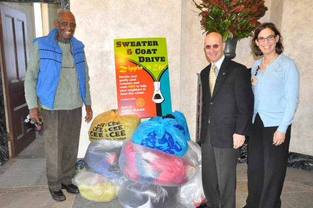 Harry Bright and Bill Fishman receive bags of collected coats and jackets from Alissa Kosowsky on behalf of the employees at NewYork-Presbyterian/Westchester Division.