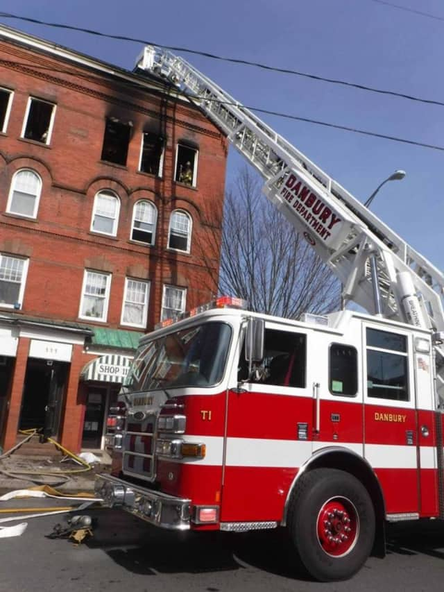 Danbury firefighters on the scene of a fire at an apartment building on Main Street Sunday afternoon.