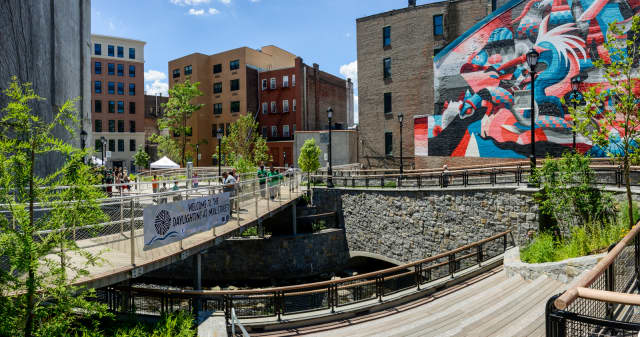 A sign welcomes visitors to the Daylighting at Mill Street, a public courtyard at the Saw Mill River in Yonkers.