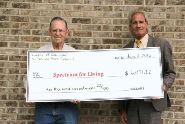 Mike Carpenter, Knights of Columbus St. Thomas More Council #2188 member and Spectrum for Living parent (left) presents a check for $6,071 to Mark Michelson, president and CEO of Spectrum for Living.