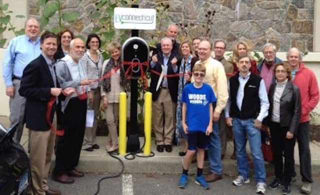 Fairfield First Selectman Michael Tetreau (back row, fifth from left) shows off one of the Town of Fairfield's electric vehicle charging stations at Fairfield Woods Library. Fairfield has encouraged electric vehicles in recent years.