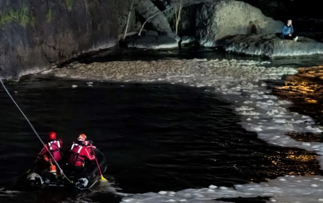 City firefighters head toward the man at the base of the Great Falls in Paterson.