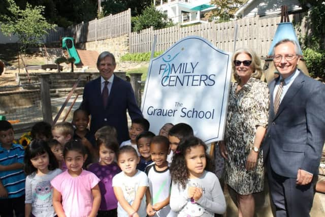 Peter (left) and Laurie Grauer join Family Centers President Bob Arnold (right) and a group of pre-schoolers at the dedication of The Grauer Preschool.