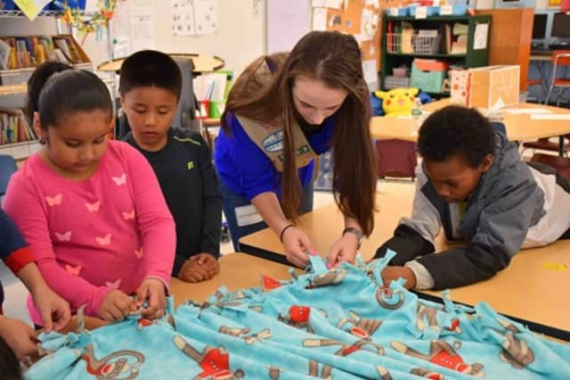 Students at the Carrie E. Tompkins Elementary School in Croton-on-Hudson help Yorktown Girl Scout Alyssa Giannasca make a fleece blanket for patients at Blythedale Children's Hospital in Valhalla.