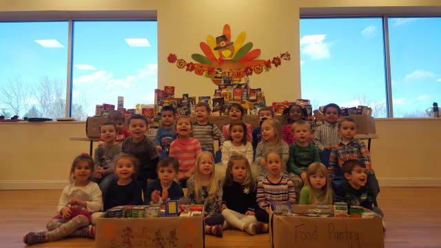 Children at the Goddard School in Yorktown show off some of the food they collected for needy families.
