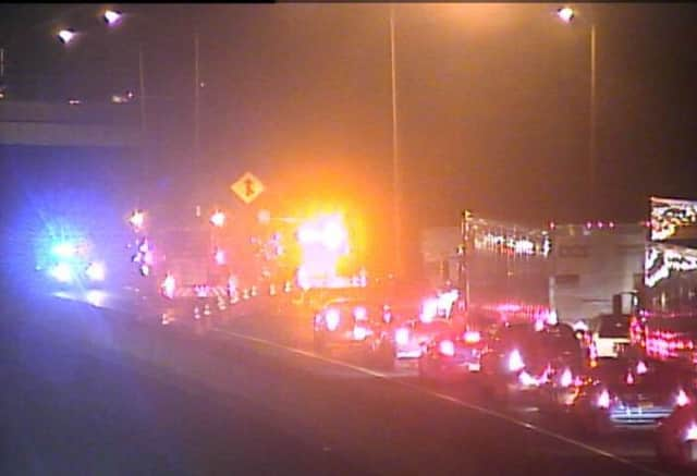 Emergency responders at the scene of a deadly crash on I-95 in Westport on Wednesday night. The driver of a truck was killed in a fiery rollover crash. A man driving a car that clipped the truck was charged with DUI.
