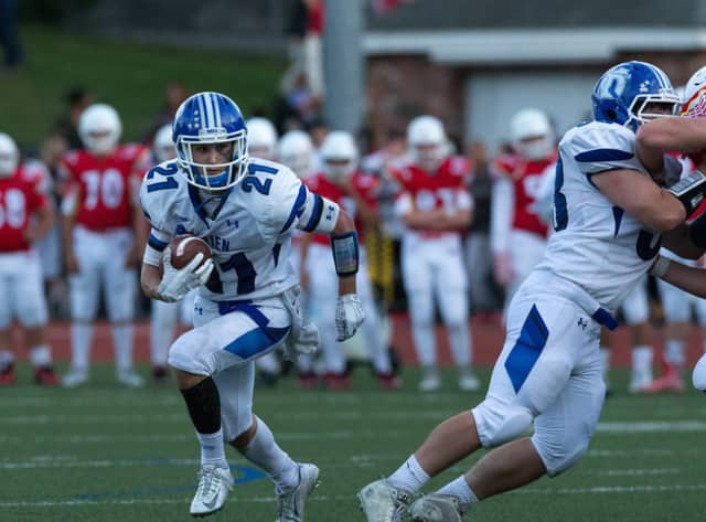 Darien's Shelby Grant runs behind a blocker during Saturday's win over Greenwich. He set a school record with six touchdowns.