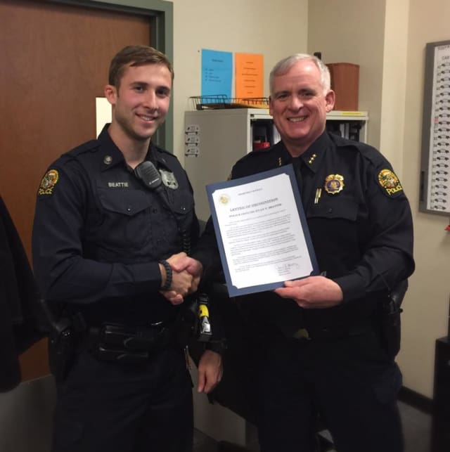 Officer Ryan Beattie receives the Officer of the Month Award from Police Chief Jim Heavey