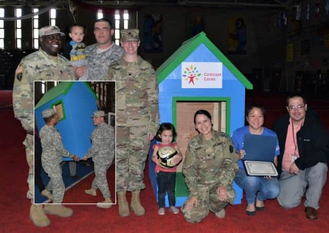 Spc. Adriana Garcia of the 250th Brigade Support Battalion and her children, Arianna, 3, and Adam, 2, with the donated playhouse.