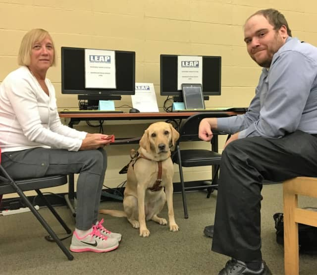 Technology Trainer Kevin Rutan with Paula Webber, technology center user, and her guide dog, Abby.