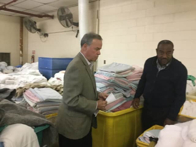 County Executive Ed Day and Renold Julien look over surplus items at the Summit Nursing Home that could be donated to help relief efforts in Haiti following Hurricane Matthew.
