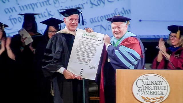 CIA President Tim Ryan presenting Anthony Bourdain with an honorary doctorate from The Culinary Institute of America.