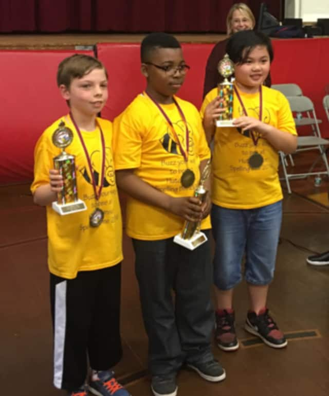 Principal Carla Tarazi proudly looks on at three spelling bee winners holding their trophies.