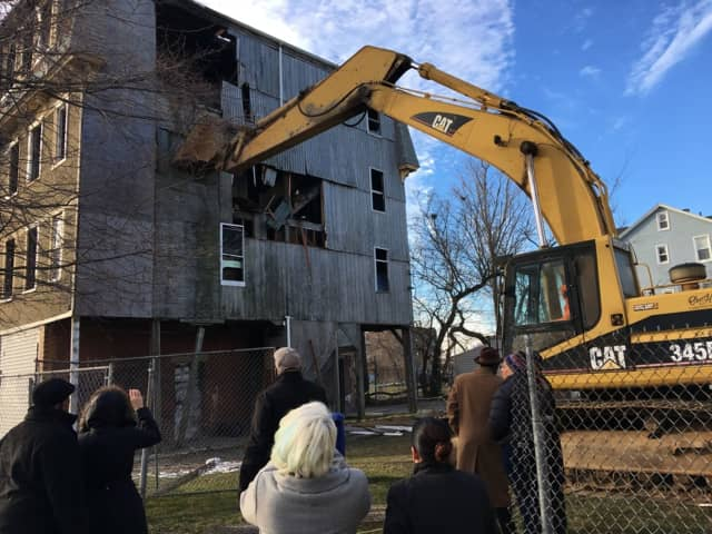 Local politicians look on as workers dismantle a vacant building in Bridgeport's East End.