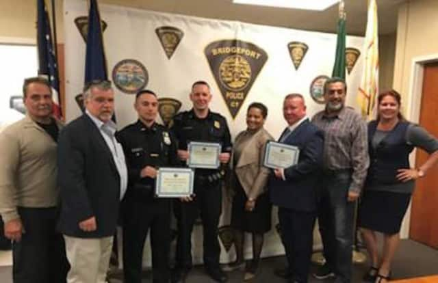 Members of Board of Police Commissioners present three Bridgeport Police officers with the Merit Award for Excellent Arrest. See story for IDs.