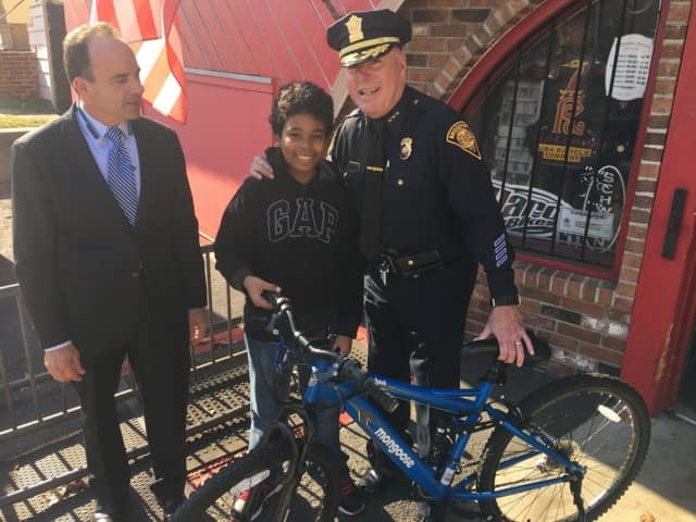 Bridgeport Mayor Joe Ganim, left, and Police Chief AJ Perez, right, present assault/theft victim Kyle Marrero with a new bike bought by detectives who investigated his case.