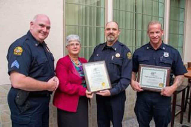 Public Affairs Manager Fran Mayko, center, left, presents Greenwich police Lt. John Slusarz with a Gold Award; and Officer Dan Hendrie, right, with a Traffic Safety Hero award. At left is Sgt. Patrick Smyth.