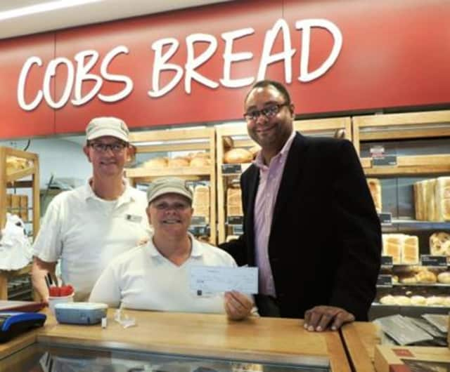 COBS Bread Franchise Owners Rob and Louise Hyden present their donation to Alan Mathis.