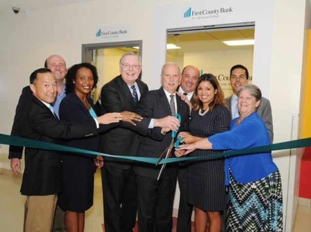 Representatives of First County Bank and Stamford Public Schools perform the ribbon-cutting ceremony, officially opening the bank's new limited access branch at the Academy of Information Technology and Engineering in Stamford.