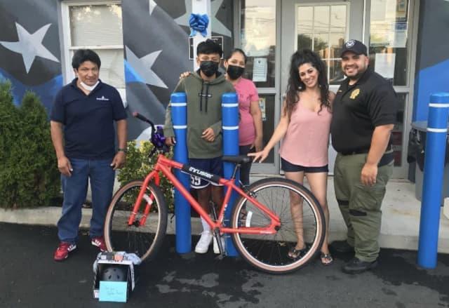 The boy with his folks, left, Sherry Solomov, Bogota Police Detective Devin Rivera.