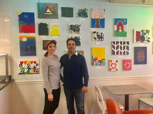 Charly Sahlia and Jazmine Damato, an employee of UCBC Darien, standing in UCBC storefront surrounded by art by Tiny Miracles foundation, which helps families with premature babies.