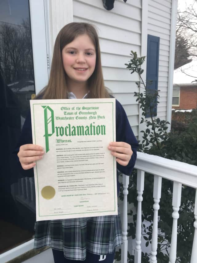 Jennifer Reilly proudly displays a proclamation from the Town of Greenburgh.