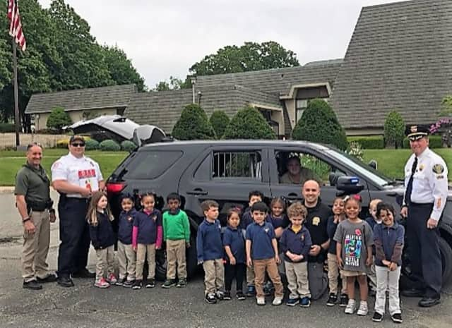 (FROM LEFT): SRO Francisco Sanchez, Capt. Martin Gray, Detective Anthony Koptyra, Lt. John Lesica (in SUV) and Chief Raymond Kovach with the pre-schoolers.
