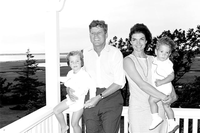 President John F. Kennedy and first lady Jacqueline Kennedy pose for a portrait with their children, Caroline Kennedy and John F. Kennedy Jr., on a porch in Hyannis Port, Massachusetts. Courtesy Cecil Stoughton. White House Photographs. John F. Kennedy Presidential Library and Museum, Boston.