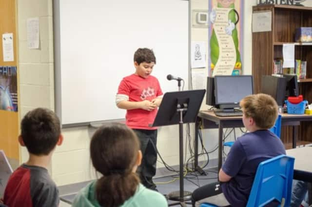 A student author reads from his written work to a peer audience at Link Elementary School.