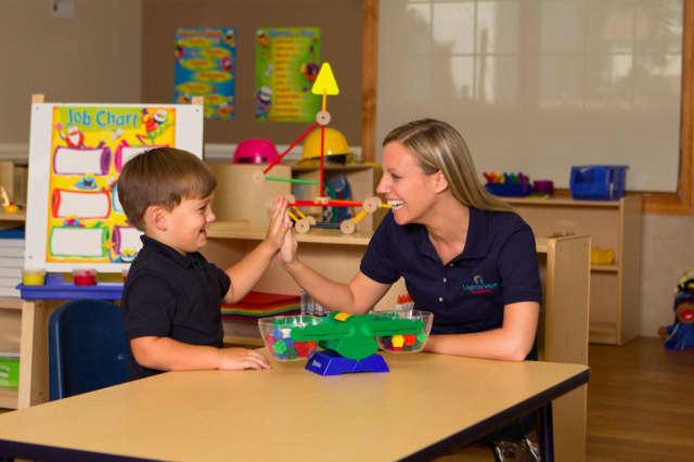 A Lightbridge Academy teacher and child share a high five.