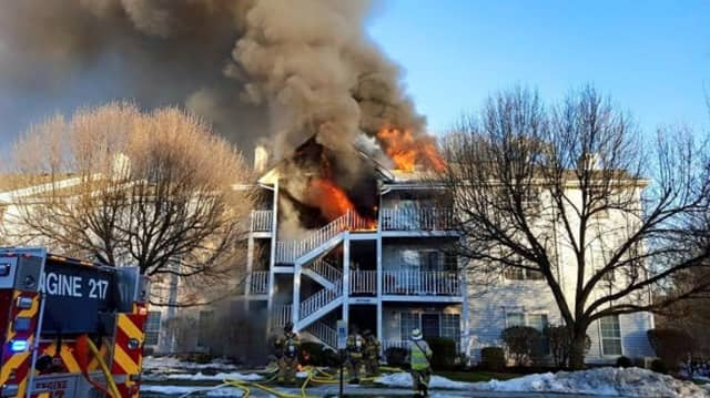Flames erupt from the Society Hill Village condominium complex on Juniper Way in Mahwah, N.J., on Tuesday, Feb. 2. Three police officers saved the life of a little girl by convincing her to jump for a third-floor balcony into their arms.