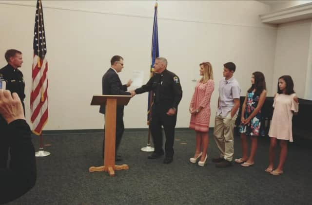 Massimo D'Elia is sworn in by Commissioner Rich Colangelo in front of his wife and kids while Chief Tim Shaw looks on